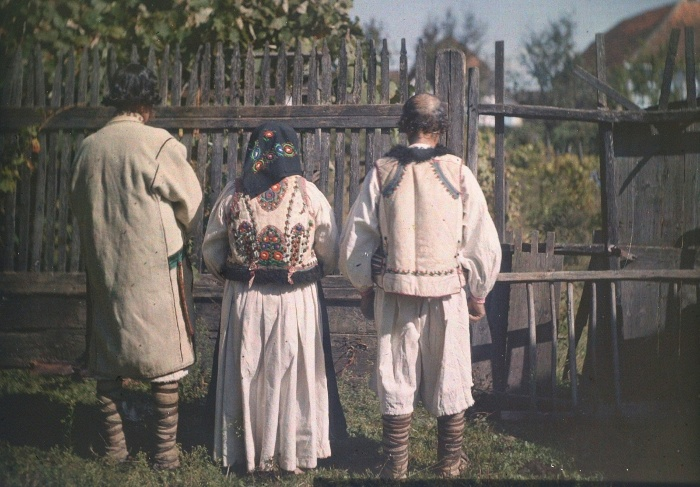 Romanian men in laced slippers and felt outerwear, Romanian woman in a leather waistcoat Tatárfalva, Romania. Taken by István Györffy, 1911, colour, autochrome plate, 13x18 cm.  Museum of Ethnography, D 4982